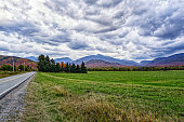 A rural highway in northern New York State runs straight along the edge of an agricultural meadow, with a view of the Adirondack Mountains and a stormy autumn cloudscape in the distance.
