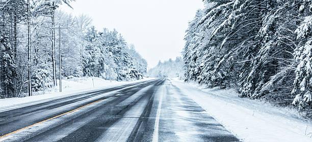 remote rural winter highway straitaway in blizzard snow storm - snötäckt bildbanksfoton och bilder