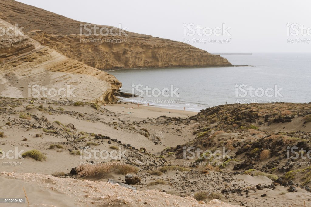 Remote sand beach in volcanic landscape in summer stock photo
