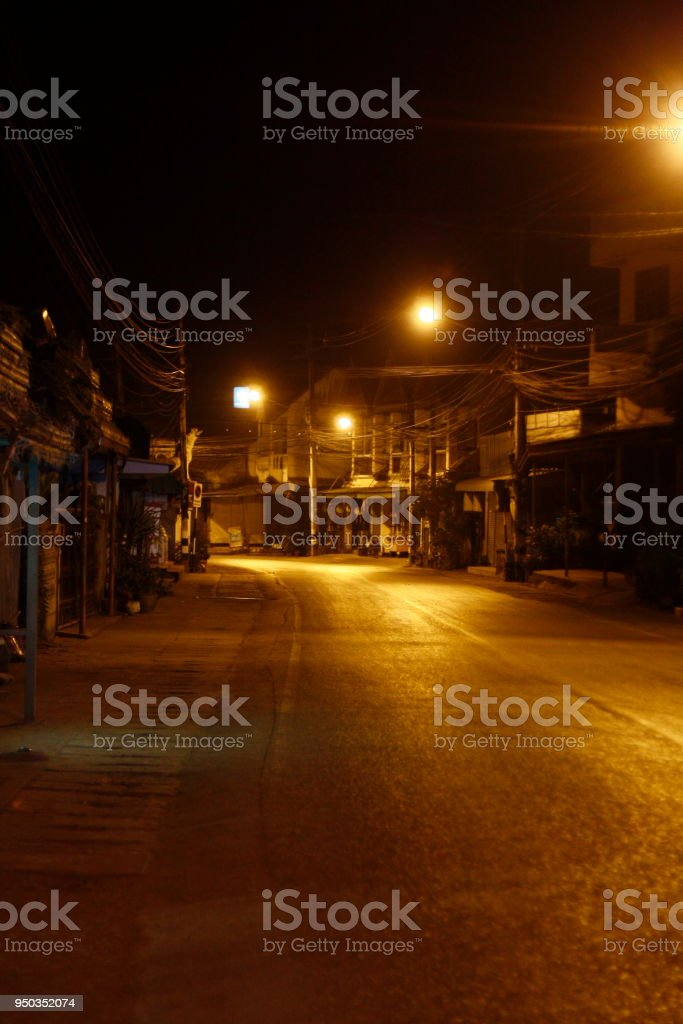 remote thai town main street at night time with rows of yellow...