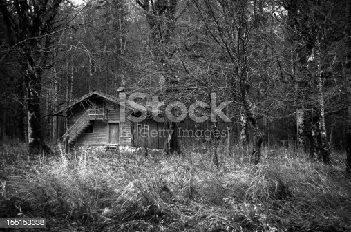A black and white view of a small wooden cabin in the middle of a wooded area away from any residential homes. Image taken in HDR with an added vignette for effect.