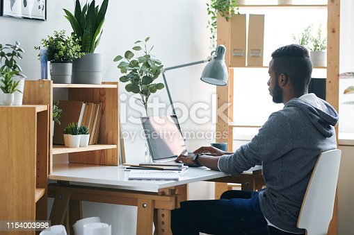 Casual young mixed-race businessman looking at laptop display while sitting on chair by desk and concentrating on remote work