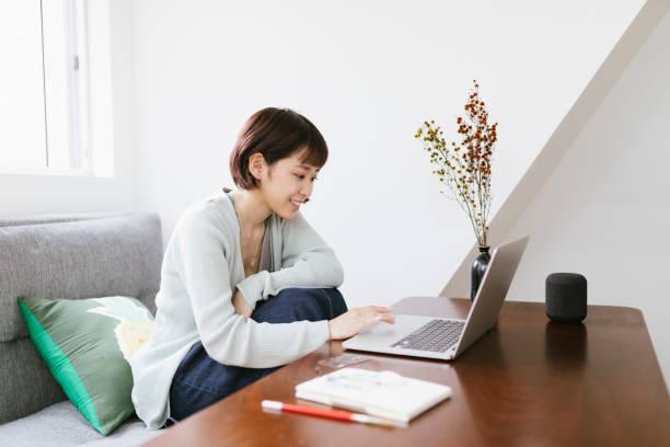 リモートワーキング - ホームオフィスで働く若いアジア人女性 - people of color ストックフォトと画像