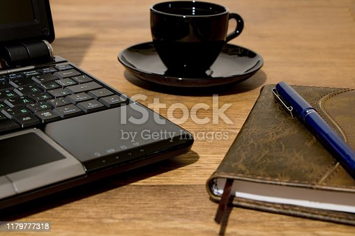 Remote workplace. Remote work environment. View of a natural wood table with several items, a black laptop, a cup of coffee, a diary and a pen.