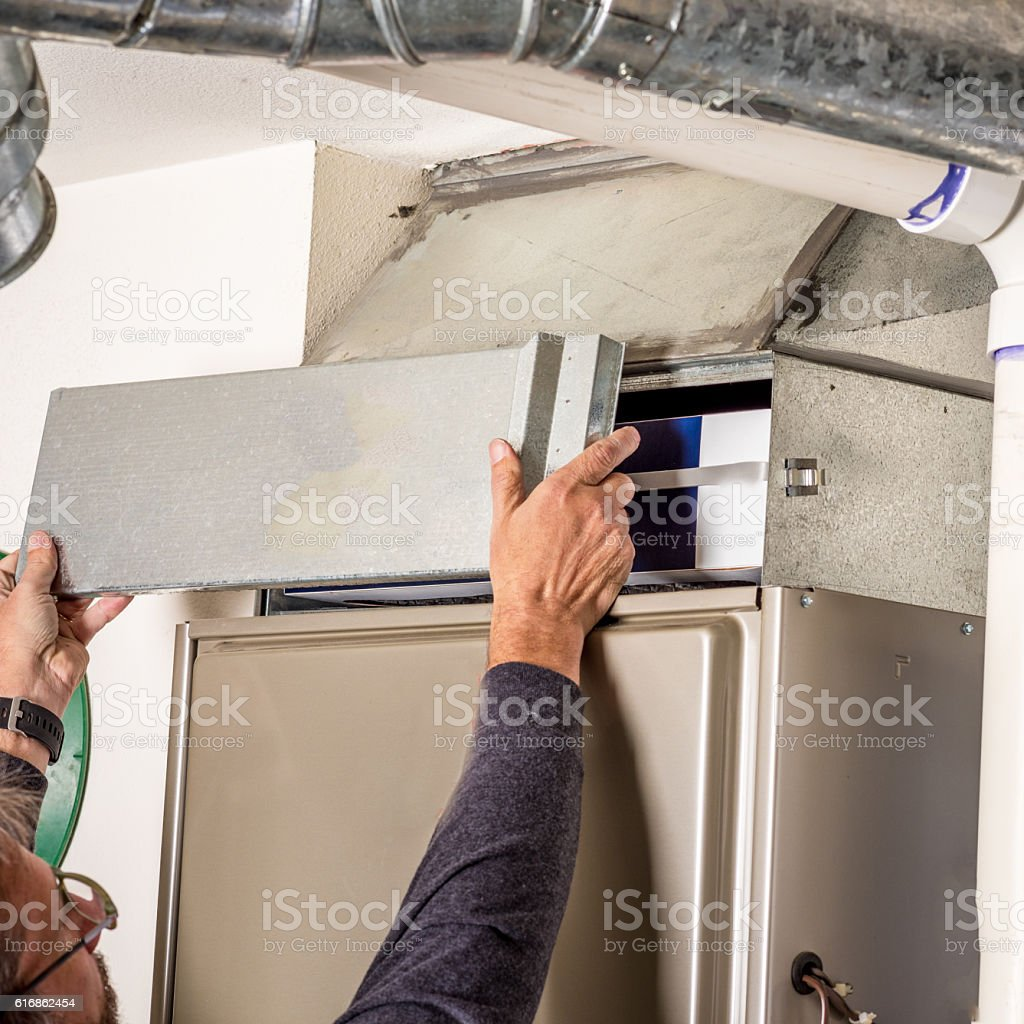 Removal of furnace access door for filter stock photo