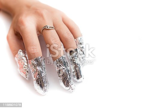 istock Removal of gel nail polish using a foil. Isolated on white. 1158601078