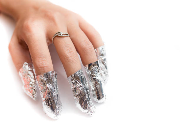 Removal of gel nail polish using a foil. Isolated on white. stock photo