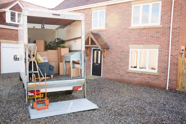 Removal Truck Waiting To Be Unloaded Outside New Home On Moving Day stock photo