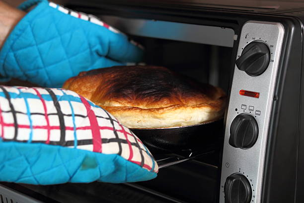 remove freshly baked pie from oven - burned oven imagens e fotografias de stock
