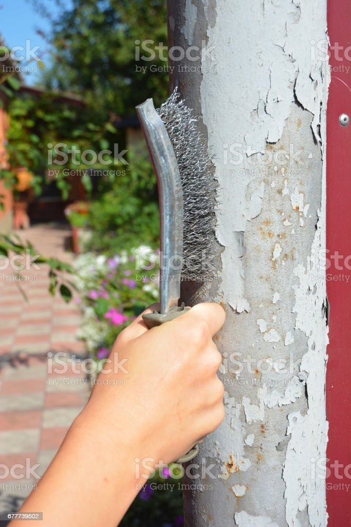 Remove the old paint from the metal fence column. Use a wire brush to strip the paint from the old metal surface. stock photo