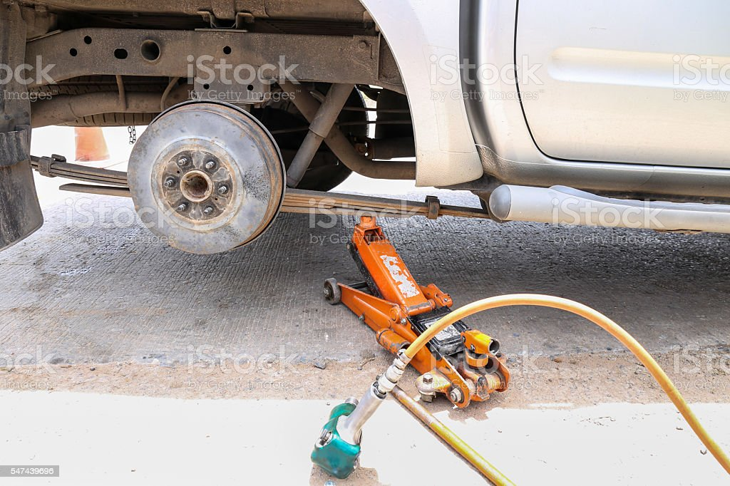 remove wheel by car jack for repair with tool stock photo