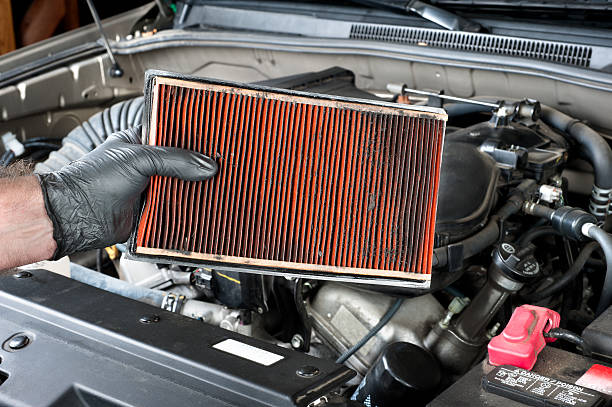 Removing a dirty automotive air filter An auto mechanic wearing protective work gloves holds a dirty, clogged air filter over a car engine during general auto maintenance. air filter stock pictures, royalty-free photos & images