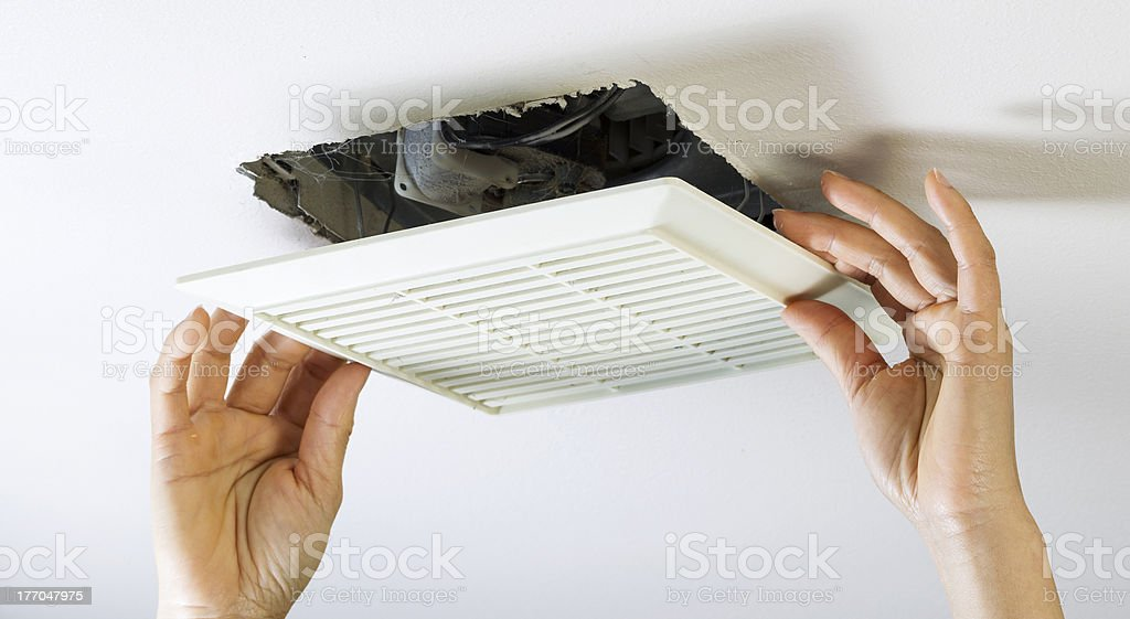 Removing Bathroom Fan Vent Cover to Clean Inside stock photo