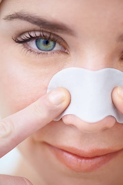 Removing blackheads in one quick pluck stock photo