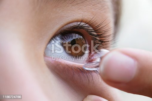 A person removing a contact lens from the eye.