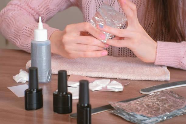 entfernen von gel polish von nägeln. frau gießt entfernen flüssigkeit auf ein wattepad, legt es auf einen nagel und wickelt die folie. close-up hände. - gelnägel stock-fotos und bilder