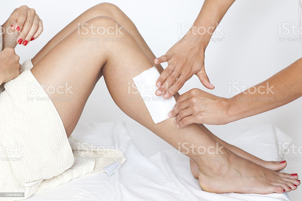 Removing hair from woman's legs royalty-free stock photo