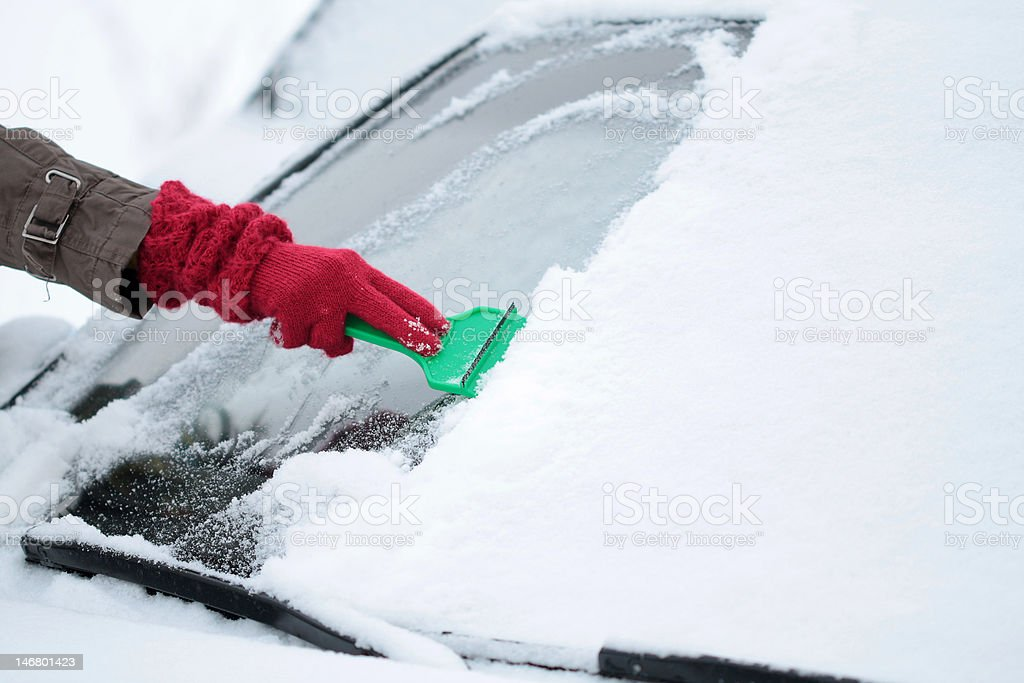 Removing Ice and Snow from the Car windshield royalty-free stock photo