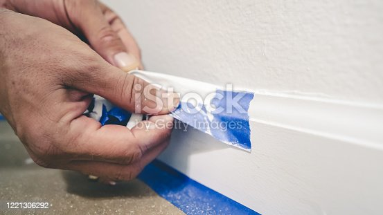 istock Removing masking tape from moulding. A painter pulls of blue painter's tape from the wall to reveal a clean edge baseboard. 1221306292