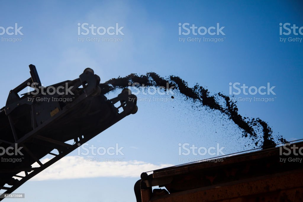 Removing old asphalt and throwing it on a truck stock photo