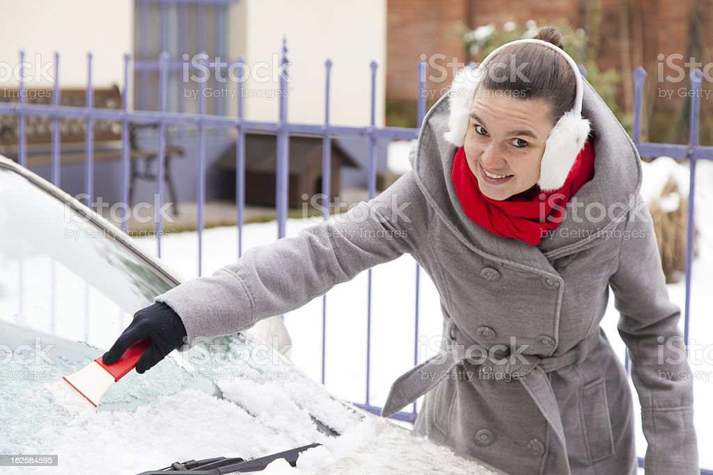 Removing snow and ice from the car royalty-free stock photo