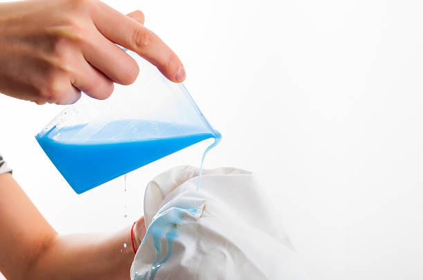 removing stain from white shirt measuring determent by hand - fleckenentferner stock-fotos und bilder