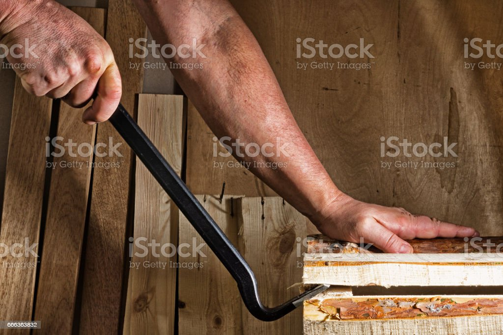 Removing the box with the help of nail puller stock photo