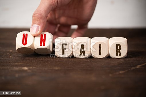 922107104istockphoto Removing two blocks with letters to change the word unfair to fair 1161282955