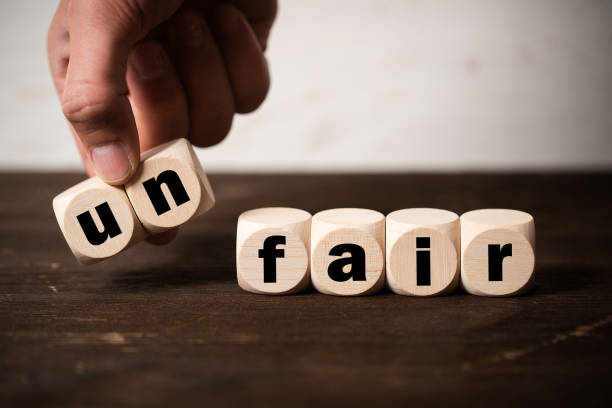 Removing two blocks with letters to change the word unfair to fair hand is removing two blocks with letters to change the word unfair to fair on wooden background discriminatory stock pictures, royalty-free photos & images