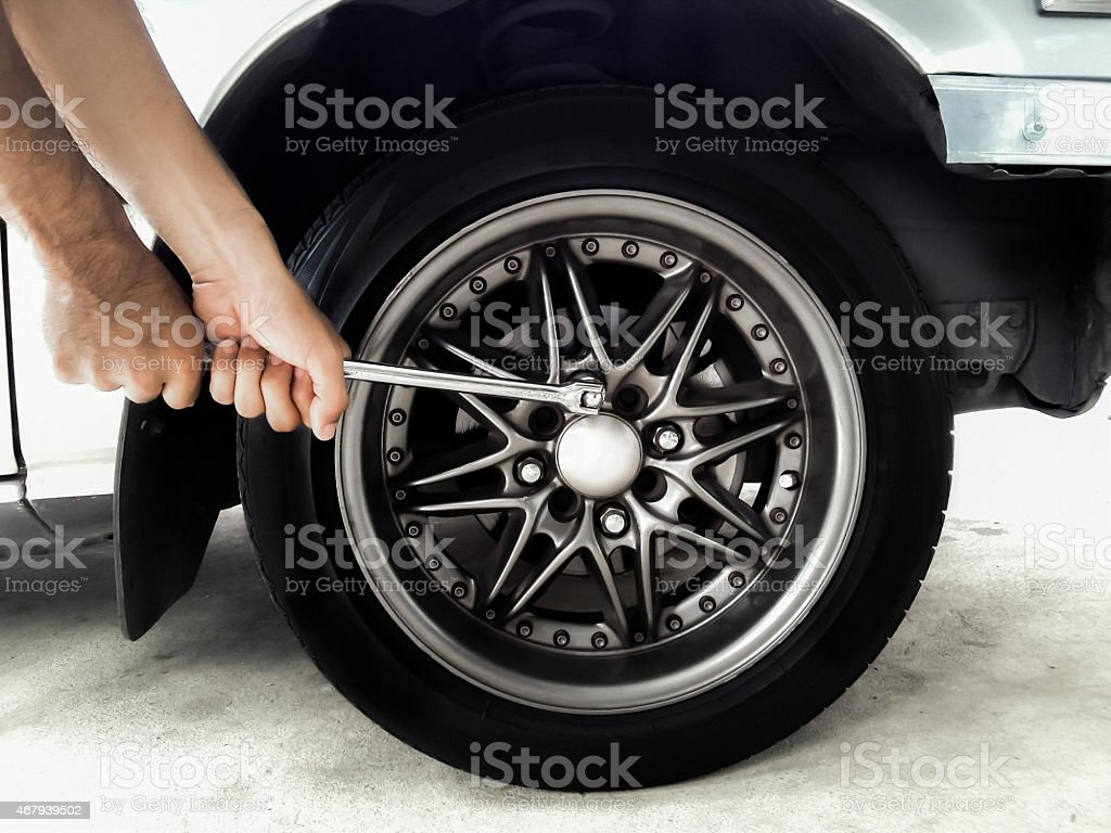 removing wheel nuts by hand wrench stock photo