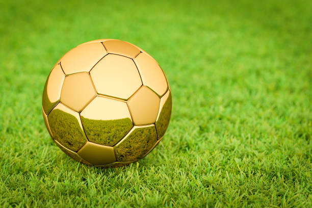 3d rendering: golden soccer ball / football lying on grass in a stadium, big business in sports, football, soccer. - soccer league stock pictures, royalty-free photos & images