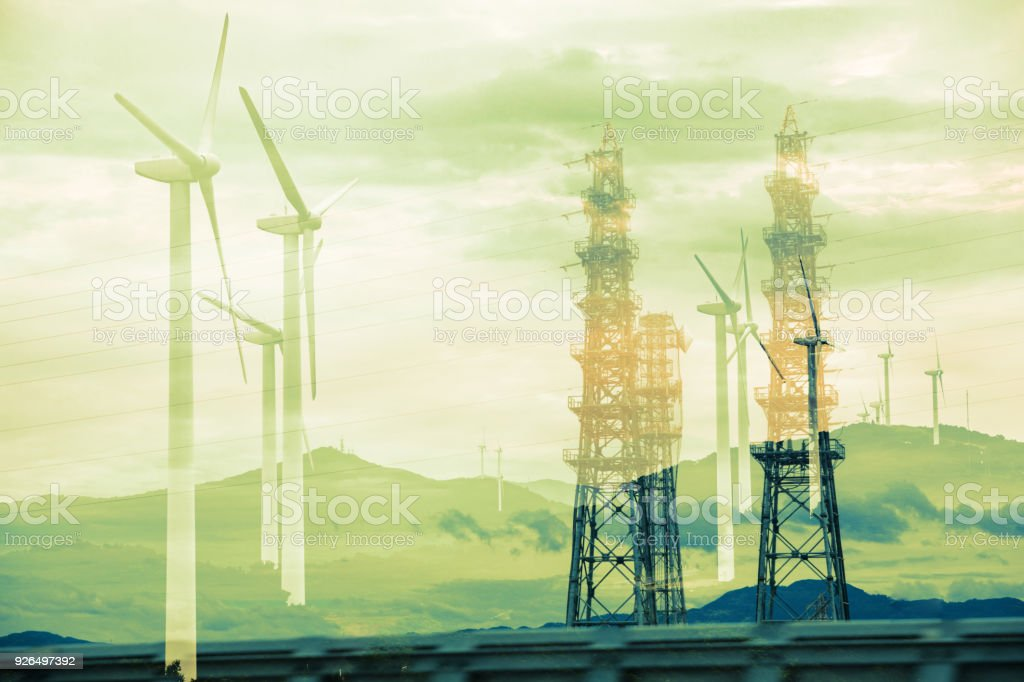 Renewable energy concept. Double exposure of Wind mill and?transmission towers. stock photo