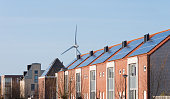 terraced houses with solar panels in front of a large windmill