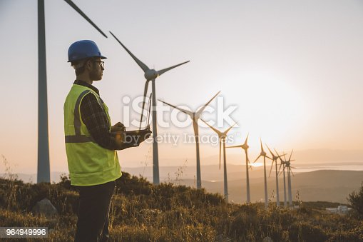Silhouette of young male engineer holding laptop computer planning and working for the energy industry and standing beside a wind turbines farm power station at sunset time. XXXL size taken with Canon 5D MIV