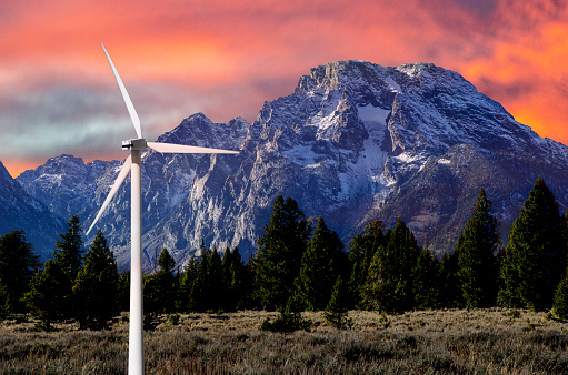 Renewable: Wind Power, Clean, Renewable Energy Wind Turbines in front of the Grand Teton Range against a dramatic sky during Sunset