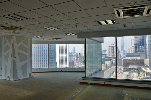 Empty, big open-space office room with panoramic view at modern city in China. During remodeling improvement work.