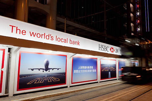 HSBC Renminbi bonds advertisement Hong Kong, China - August 24, 2011: A tram move past next to an advertisement for Renminbi bonds in Queen\'s Road, Central District, Hong Kong. Chinese Vice Premier Li Keqiang reaffirmed the Hong Kong\'s status as a hub for Beijing\'s ambitious goal to turn the Renminbi into a global currency. hsbc stock pictures, royalty-free photos & images