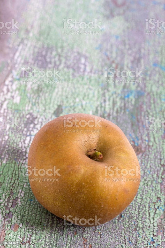 Rennet apples is a very old variety with a pleasant mild dry flavour old green painted wooden board stock photo