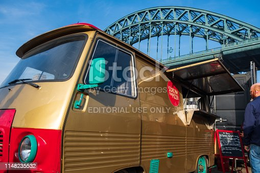 Newcastle, United Kingdom - February 23, 2019: A rennovated classic van is used as a portable canteen serving pizza at Gateshead, Newcastle with Tyne Bridge in the background