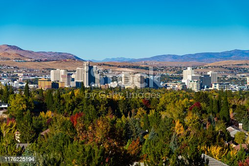 Downtown Reno skyline in the distance during Autumn, and with mountain ranges in the background, and a residential area with lush trees, including Autumn colored trees, in the foreground.
