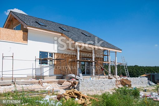 1070686034 istock photo Renovate and repair residential house facade wall with stucco, insulation,plastering, painting wall. House construction with asphalt shingles roof, skylights, terrace patio. Modern home construction 917747604