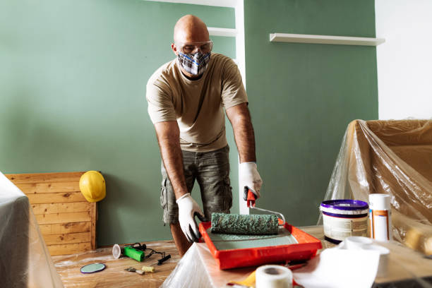 Renovation at home - man preparing the paint for second coat stock photo