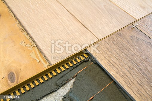 istock Renovation close-up: instalation of ceramic tiles with heating cables and wooden parquet on the floor 922081754