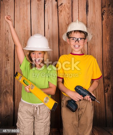 527687520 istock photo Renovation construction concept. Happy children in hardhats with tools. 487518920