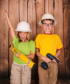 Renovation and construction concept. Portrait of happy children in hardhats with tools on wooden background.