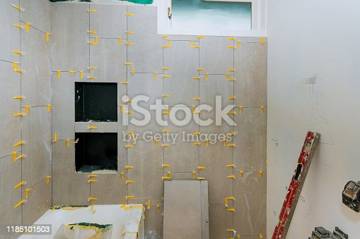 1138442636 istock photo Renovation construction laying floor and wall tile reconstruction of bathroom 1185101503