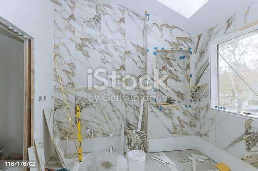 1138442636 istock photo Renovation construction laying floor and wall tile reconstruction of bathroom 1187176702