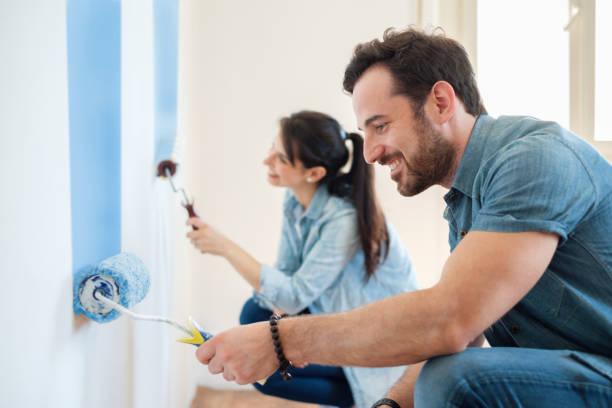 renovatie diy verf paar in nieuwe huis schilderen muur samen - verf stockfoto's en -beelden
