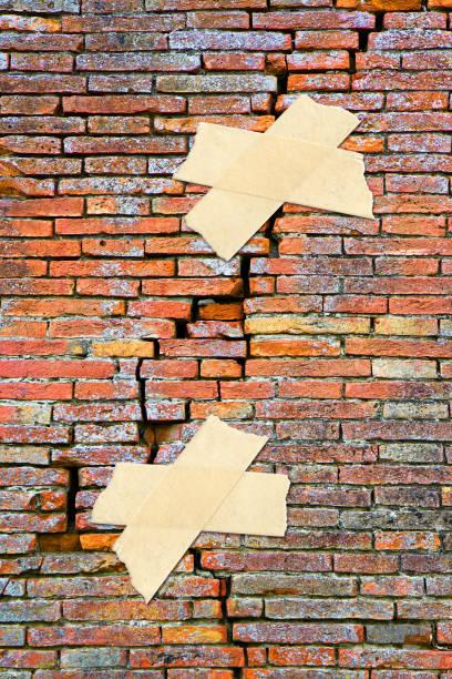 sanierung von gerissenen ziegelmauer - konzept bild mit klebeband - pflasterbau stock-fotos und bilder