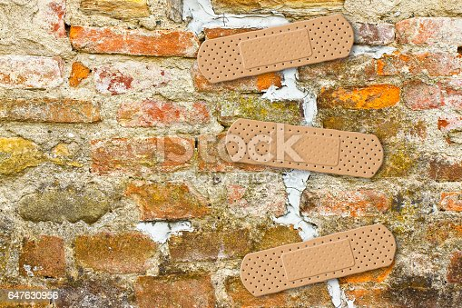 istock Renovation of cracked brick wall - concept image with copy space 647630956